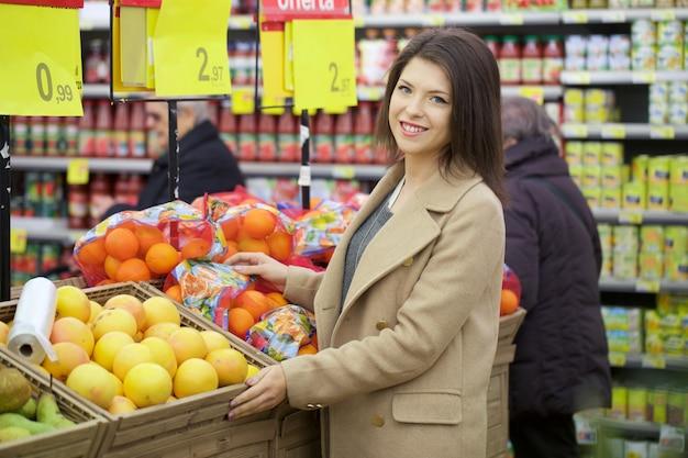 Hübsche frau, die am supermarkt kauft