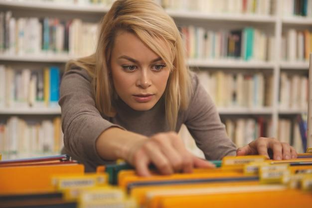 Hübsche frau, die an der bibliothek studiert