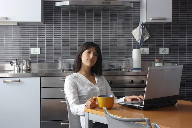 Hübsche frau, die an einem laptop in der küche arbeitet