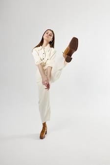 Hübsche frau, die anzug braunes schuhbein trägt, erhob studio