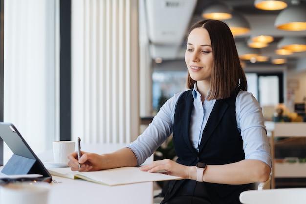 Hübsche frau, die arbeitszeitplan schreibt, der in notizbuch schreibt, während sie am arbeitsplatz mit tablette sitzt.