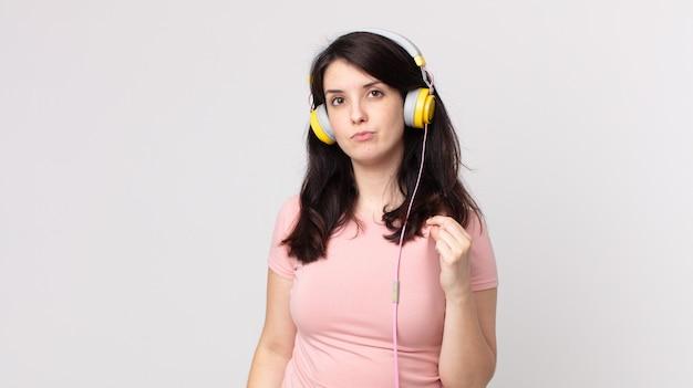 Hübsche frau, die arrogant, erfolgreich, positiv und stolz aussieht, hört musik mit kopfhörern