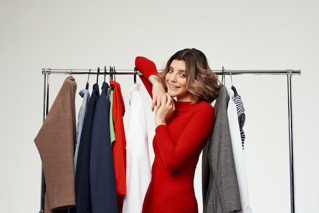 Hübsche frau, die auf bekleidungsgeschäft shopaholic hellem hintergrund anprobiert