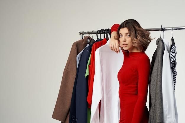 Hübsche frau, die auf bekleidungsgeschäft shopaholic isolierten hintergrund anprobiert