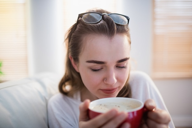 Hübsche frau, die auf couch mit kaffee im wohnzimmer sich entspannt