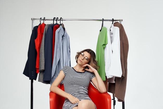 Hübsche frau, die auf dem roten stuhl nahe der garderobe sitzt, lokalisierte hintergrund
