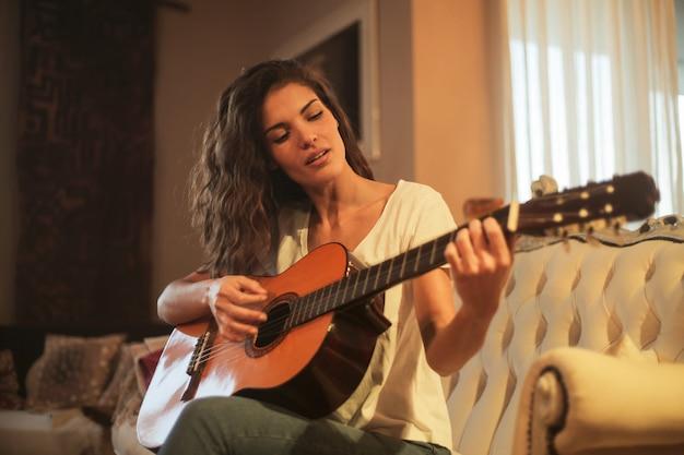 Hübsche frau, die auf einer gitarre spielt