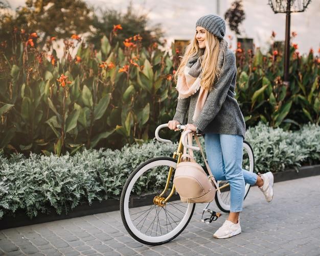 Hübsche frau, die auf fahrrad nahe blumenbeet sich lehnt