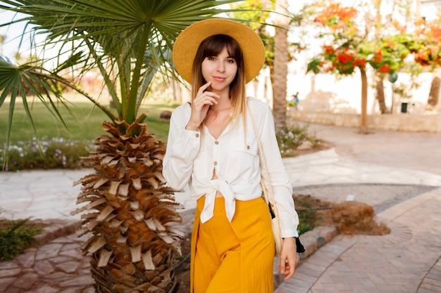 Hübsche frau, die auf palmen und blühenden bäumen steht. strohhut tragen.