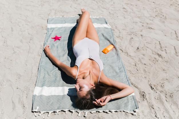Hübsche frau, die auf strand ein sonnenbad nimmt