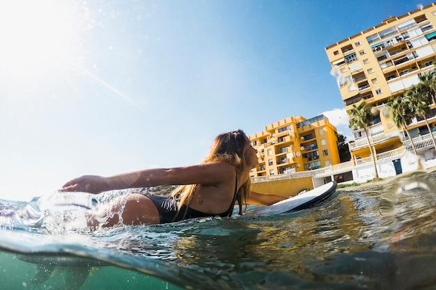 Hübsche frau, die auf surfbrett im wasser schwimmt