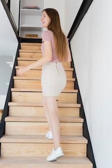 Hübsche frau, die auf treppe geht