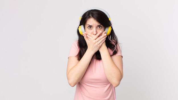 Hübsche frau, die den mund mit den händen bedeckt, mit einer schockierten musik mit kopfhörern