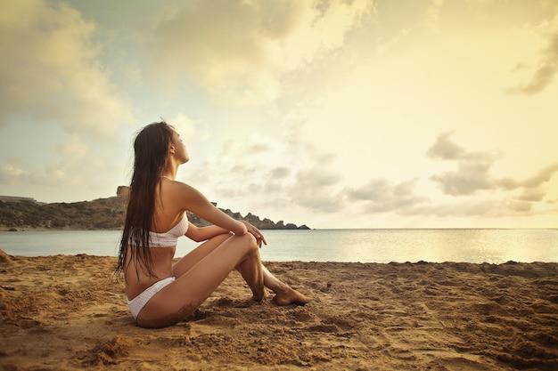 Hübsche frau, die den sonnenuntergang auf dem strand genießt