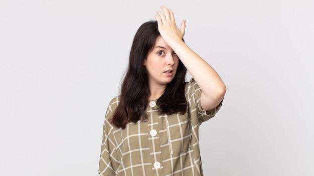 Hübsche frau, die die handfläche zur stirn hebt und denkt, oops, nachdem sie einen dummen fehler gemacht oder sich daran erinnert hat, sich dumm zu fühlen