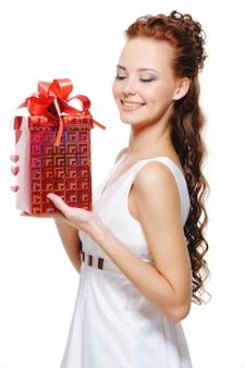 Hübsche frau, die die rote schachtel mit dem weihnachtsgeschenk in den händen hält