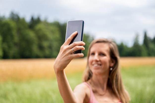 Hübsche frau, die draußen selfies macht