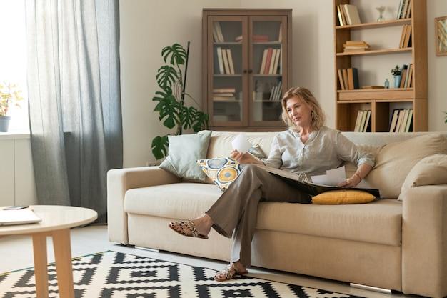 Hübsche frau, die durch fotoalbum mit bildern ihrer freunde, verwandten und sich selbst schaut, während sie auf der couch im wohnzimmer entspannt