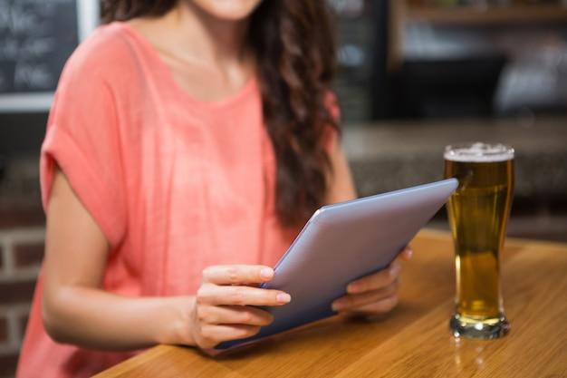 Hübsche frau, die ein bier isst und tablette betrachtet