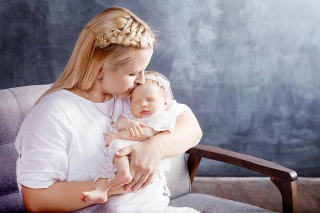 Hübsche frau, die ein neugeborenes baby in ihren armen hält. glückliche mutter und ihr rutschendes neugeborenes baby.