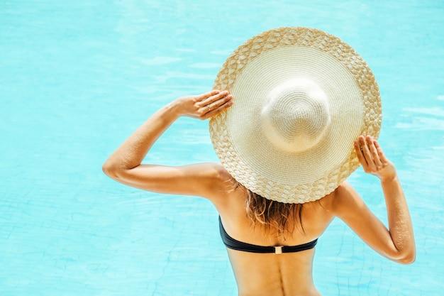 Hübsche frau, die ein schwimmbad am resort genießt
