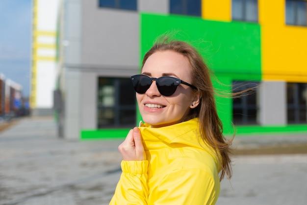 Hübsche frau, die eine gelbe jacke und eine sonnenbrille mit hellem farbgebäudehintergrund trägt
