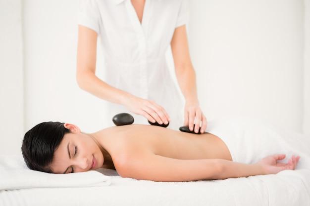 Hübsche frau, die eine massage des heißen steins empfängt