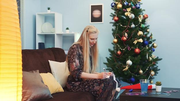 Hübsche frau, die eine postkarte nahe dem weihnachtsbaum schreibt