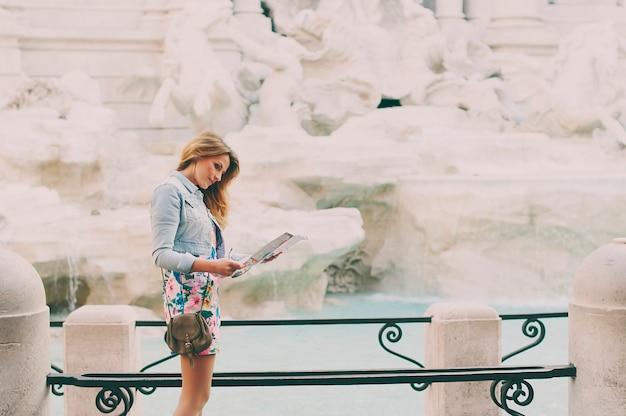Hübsche frau, die eine touristische karte nahe dem brunnen von trevi während ihrer reise in rom sucht