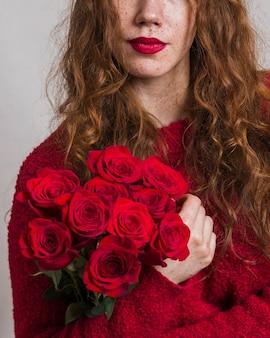 Hübsche frau, die einen blumenstrauß von rosen hält