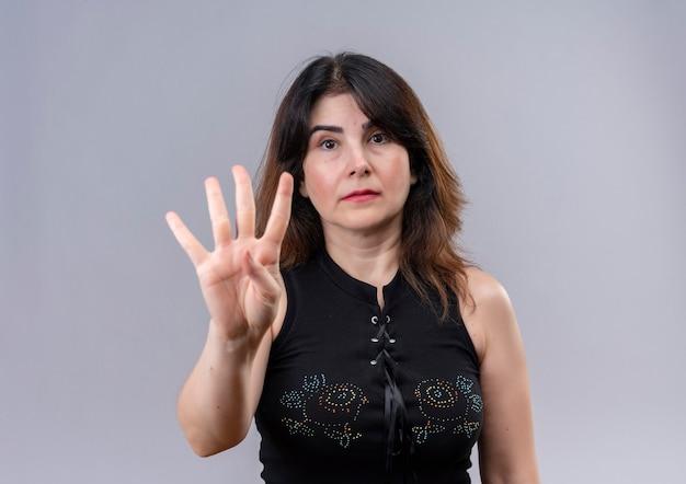 Hübsche frau, die enttäuschte schwarze bluse zeigt, zeigt mit der linken hand über grauem hintergrund