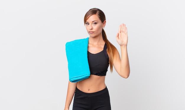 Hübsche frau, die ernst aussieht und offene handfläche zeigt, die stopp-geste macht. fitnesskonzept