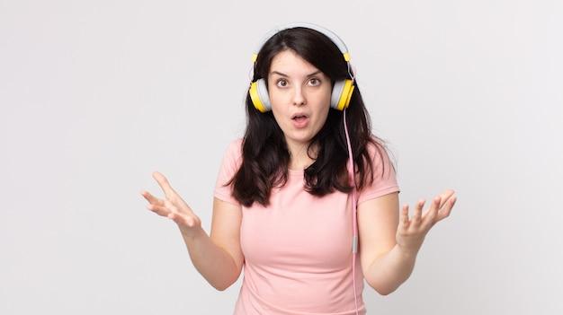 Hübsche frau, die extrem schockiert und überrascht ist, musik mit kopfhörern zu hören