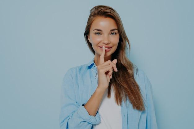 Hübsche frau, die finger auf die lippen legt und zeichensymbol macht