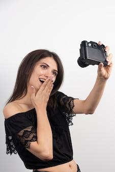 Hübsche frau, die fotos mit einer kamera macht