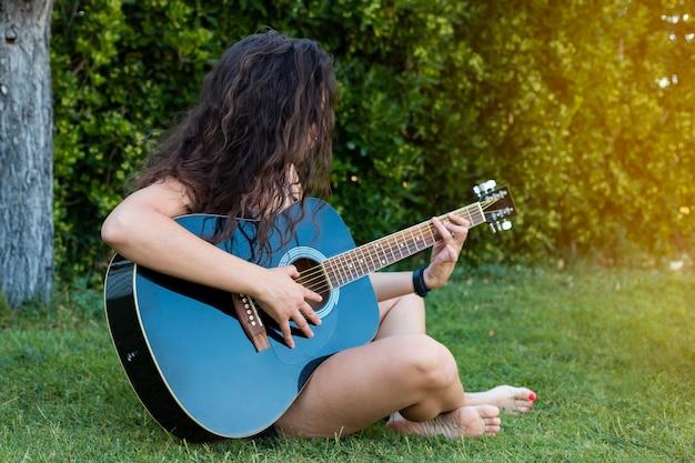 Hübsche frau, die gitarre auf gras spielt
