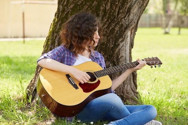 Hübsche frau, die gitarre spielt
