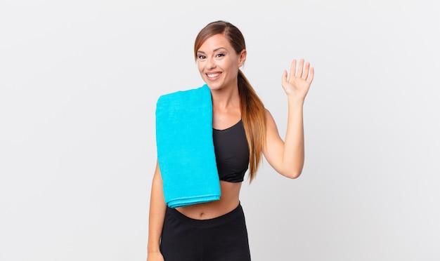 Hübsche frau, die glücklich lächelt, hand winkt, sie begrüßt und begrüßt. fitnesskonzept