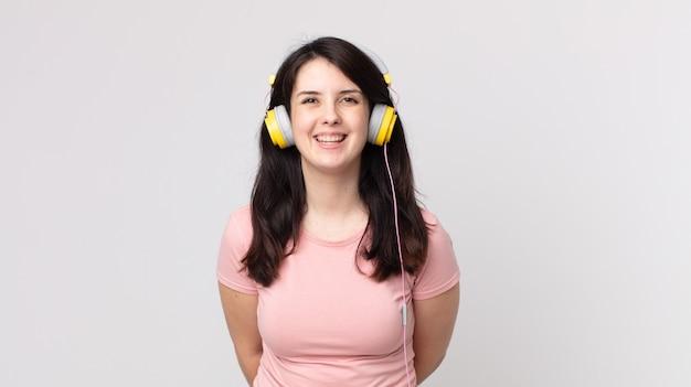 Hübsche frau, die glücklich mit einer hand auf der hüfte lächelt und selbstbewusst musik mit kopfhörern hört
