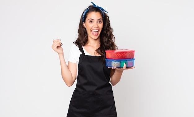 Hübsche frau, die glücklich und angenehm überrascht aussieht und tupperware mit essen hält
