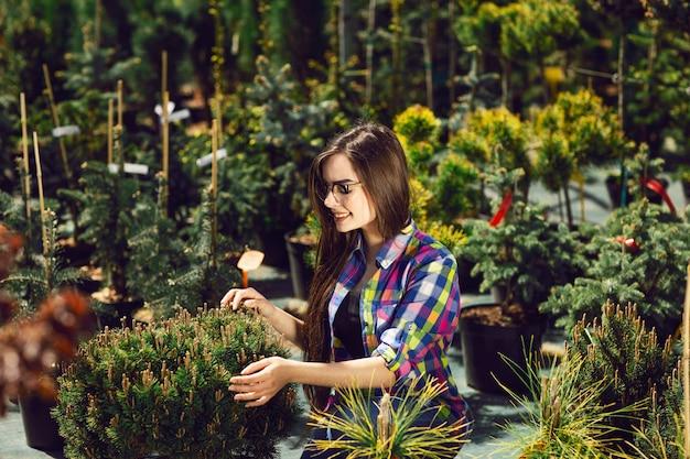 Hübsche frau, die grünpflanzen für den garten wählt und kauft.