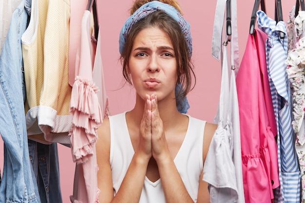 Hübsche frau, die hände zusammenhält und mit traurigem ausdruck schaut, in der nähe ihres kleiderschranks steht und sich beschwert, dass sie keine kleider hat