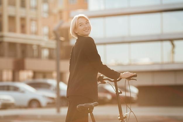 Hübsche frau, die ihr fahrrad draußen reitet