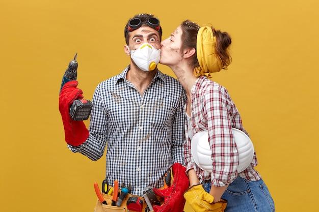 Hübsche frau, die ihren mann auf die wange küsst und ihm dankbar ist, dass er ihre garderobe repariert hat. überraschter männlicher arbeiter in maske, der bohrmaschine hält, die froh ist, kuss von seiner freundin zu erhalten