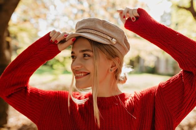 Hübsche frau, die im herbst trendige accessoires trägt. nahaufnahmefoto einer lächelnden blondine im park.