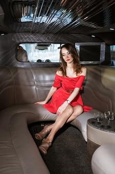 Hübsche frau, die im roten kleid in der limousine sitzt, traurig