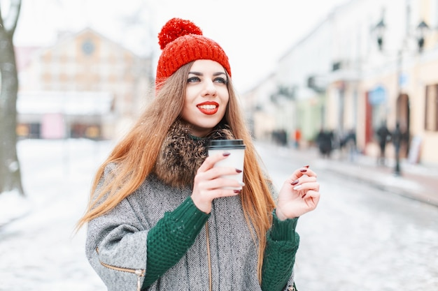 Hübsche frau, die in der stadt geht und ein heißes getränk am wintertag trinkt
