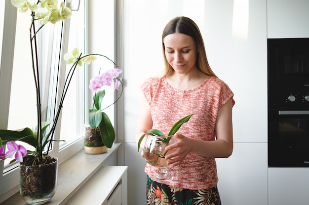 Hübsche frau, die in händen eine dose wasser mit einer orchideenpflanze hält