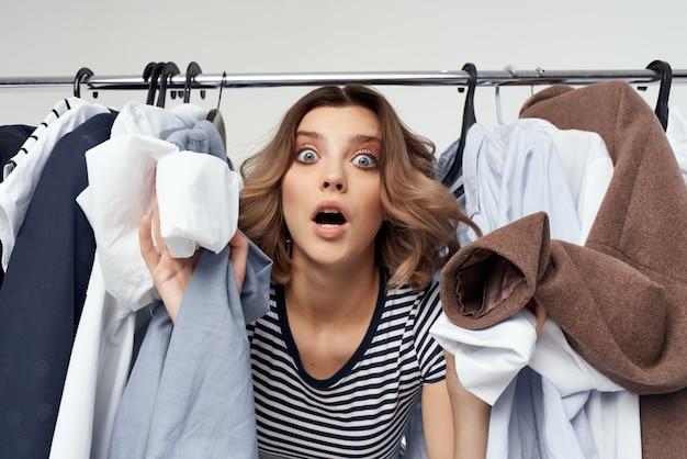 Hübsche frau, die isolierten hintergrund im bekleidungsgeschäft anprobiert