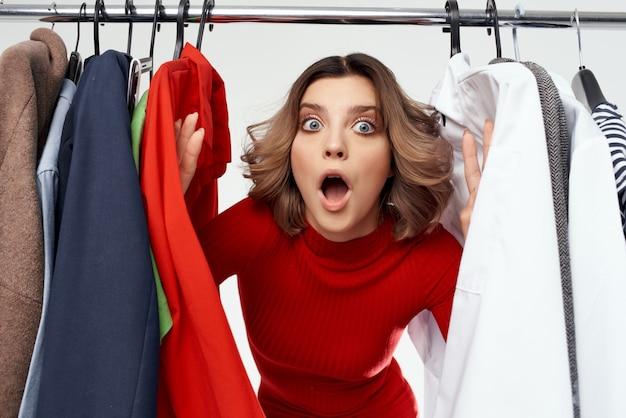 Hübsche frau, die kleidung shopaholic isolierten hintergrund anprobiert